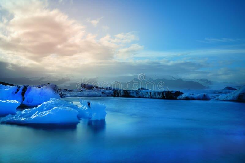 Fotografía larga de la exposición del iceberg azul que flota delante de la montaña del casquillo de la nieve imagen de archivo