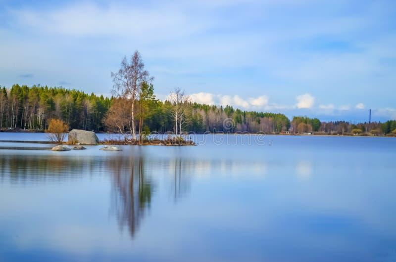 Fotografía larga de la exposición del lago del agua potable rodeada por los árboles de abedul del pino y la belleza increíble deb fotografía de archivo libre de regalías