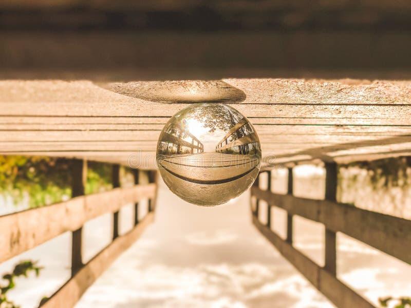 Fotografía macra de la bola de cristal redonda encima del muelle de madera de Brown fotos de archivo