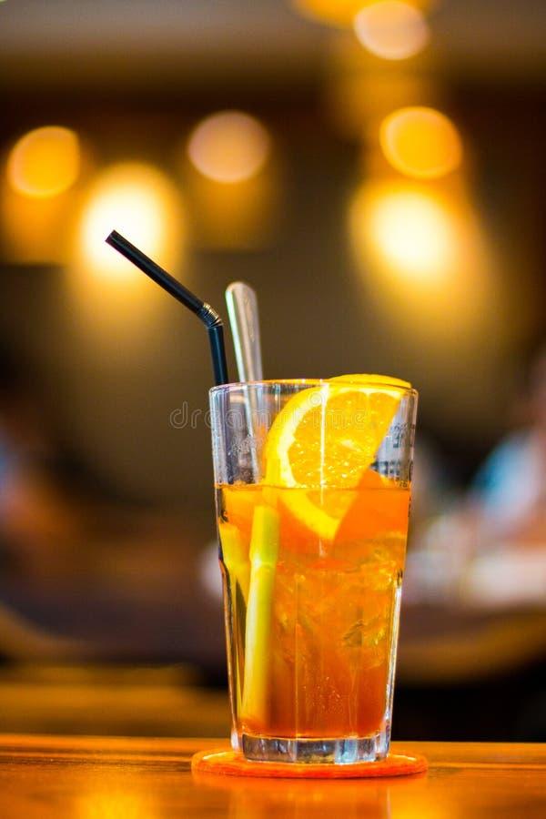 Fotografía macra del vidrio de consumición claro con la fruta del limón y la paja negra imagenes de archivo