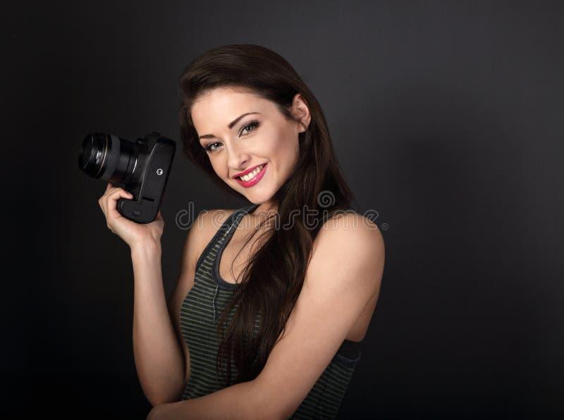 Fotografía profesional femenina joven sonriente que lleva a cabo el camer de la foto fotografía de archivo
