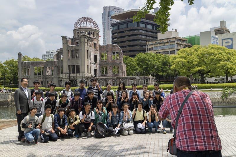 Fotografían al grupo de estudiantes en la paz Memorial Park, Hiroshima con la bóveda de la bomba atómica en el fondo foto de archivo libre de regalías