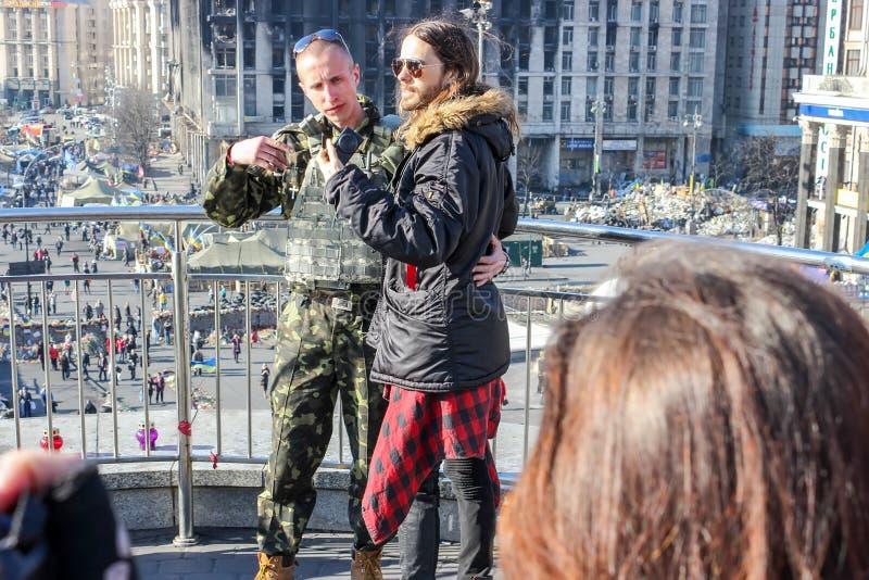 Fotograf?an a Jared Leto con los militares ucranianos contra la a quemada abajo del edificio y de un campo de la tienda sobre el  imagen de archivo