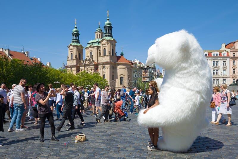 Fotografían a los turistas divertidos con un oso polar inflable gigante en la vieja plaza Praga, República Checa foto de archivo