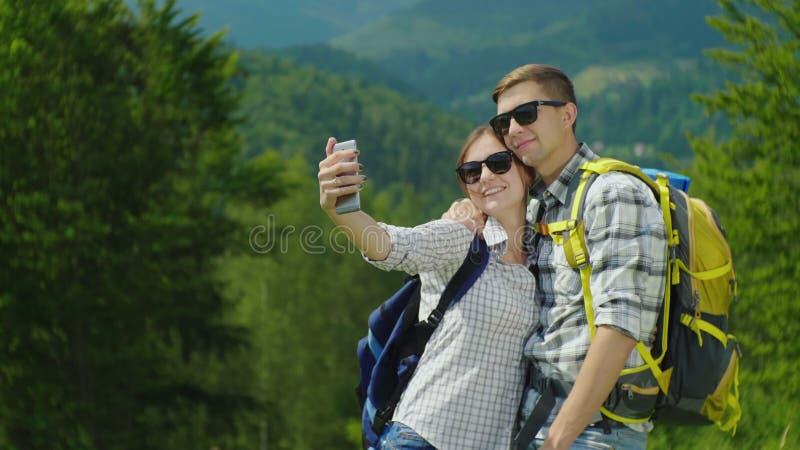 Fotografían a los turistas jovenes con las mochilas contra el contexto de un paisaje pintoresco de la montaña imagen de archivo libre de regalías