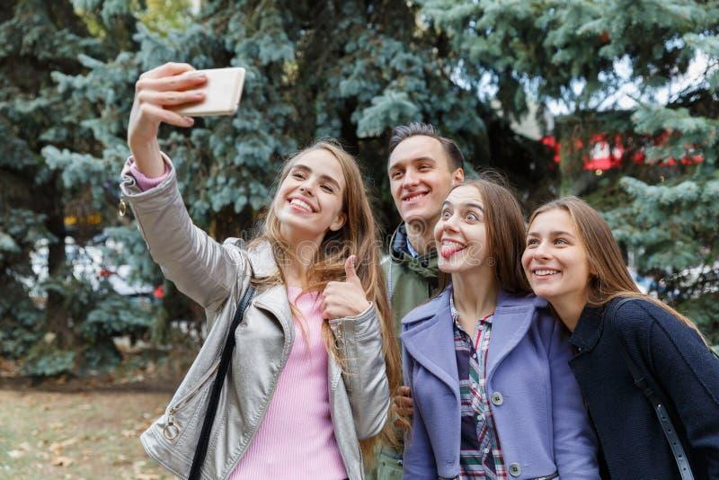Fotografían a un grupo de amigos sonrientes que toman un teléfono móvil al aire libre fotografía de archivo libre de regalías