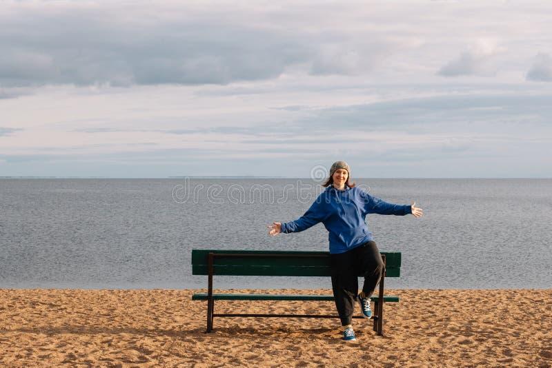 Fotografían a una chica joven en la playa en un viaje turístico que camina a lo largo de la orilla, admirando la naturaleza fotografía de archivo libre de regalías