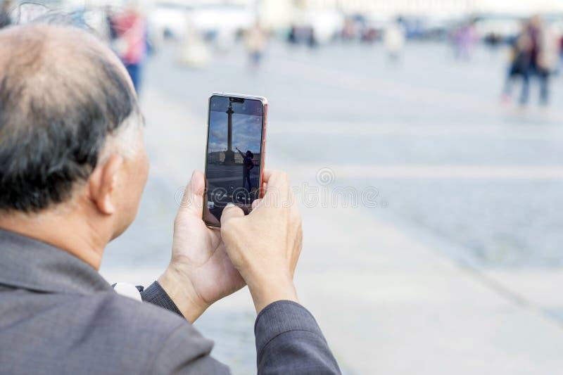 Fotografías asiáticas turísticas del aspecto del hombre en la mujer del smartphone que presenta en el cuadrado St Petersburg, Rus imagen de archivo libre de regalías