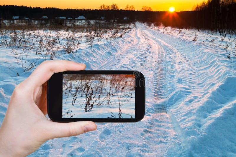 Fotografías turísticas de la puesta del sol sobre campo nevoso foto de archivo libre de regalías