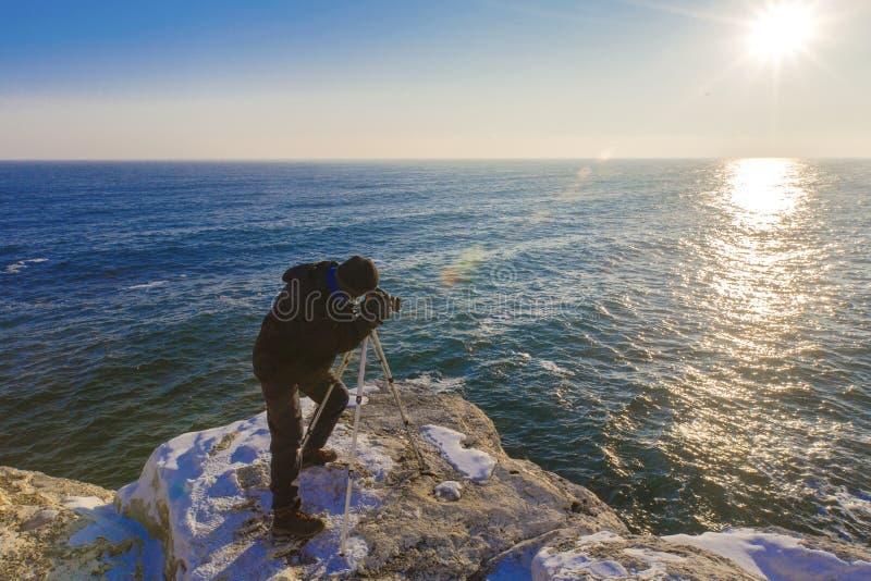 Fotograf auf den Felsen, die Landschaftsphotos machen stockfotos