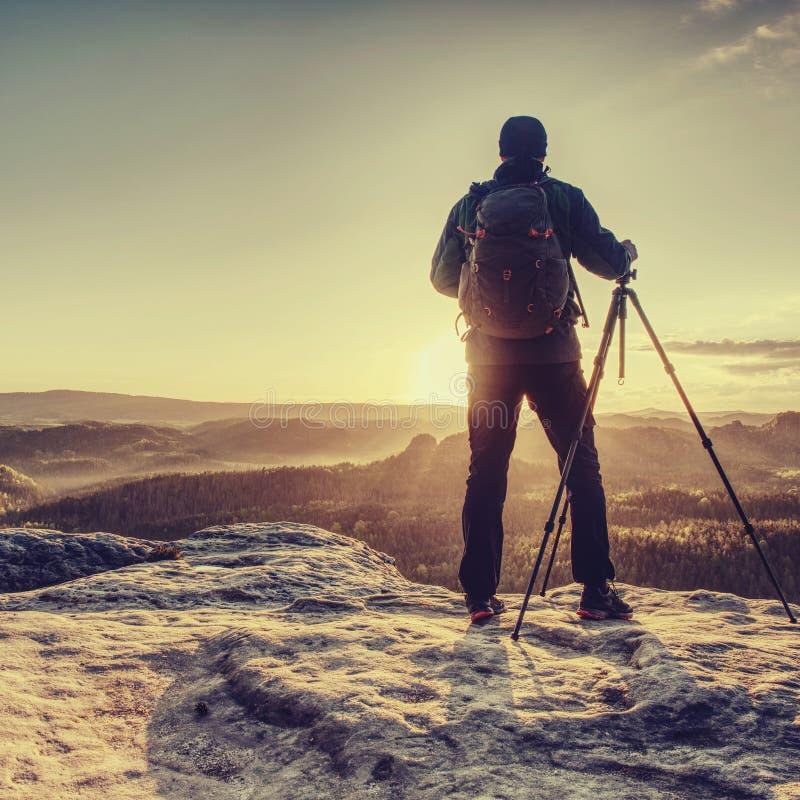 Fotograf bereitet eine Kamera und einen Stativ vor, bevor er schie?t lizenzfreie stockfotos