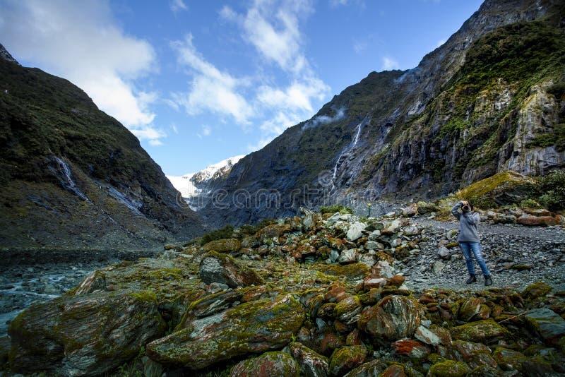 Fotograf bierze fotografię w Franz Josef lodowu jeden najwięcej popularnego podróżnego miejsce przeznaczenia w zachodnim wybrzeżu obraz stock