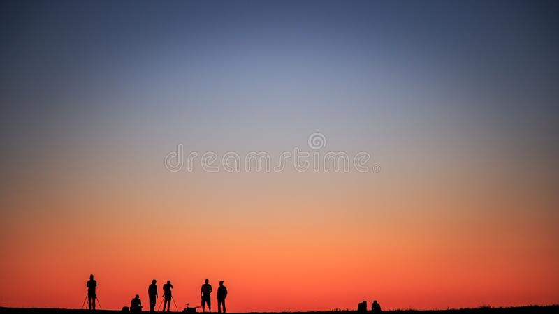 Fotograf bierze fotografię z zmierzchu niebem fotografia stock