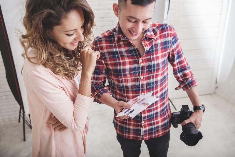 Fotograf, der das Ergebnis seines Fotodruckes zu seinem Modell ansieht stockbilder