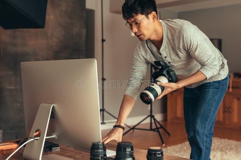 Fotograf, der die Kamera mit Computer syncing ist stockfoto