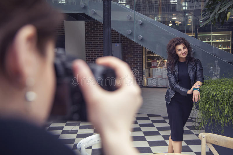 Fotograf, der eine schöne Brunettefrau auf einem Weg auf Eu schießt lizenzfreie stockfotografie