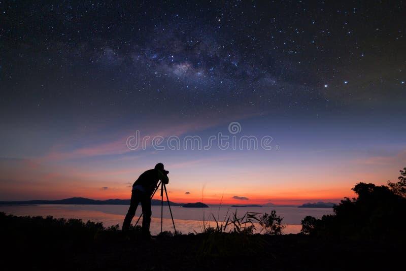 Fotograf, der Fotografiesonnenaufgang mit Milchstraßegalaxie tut lizenzfreie stockfotos