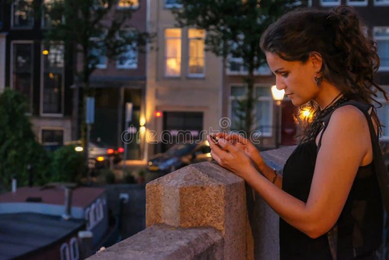 Fotograf der jungen Frau mit Smartphone auf einer Brücke lizenzfreies stockbild