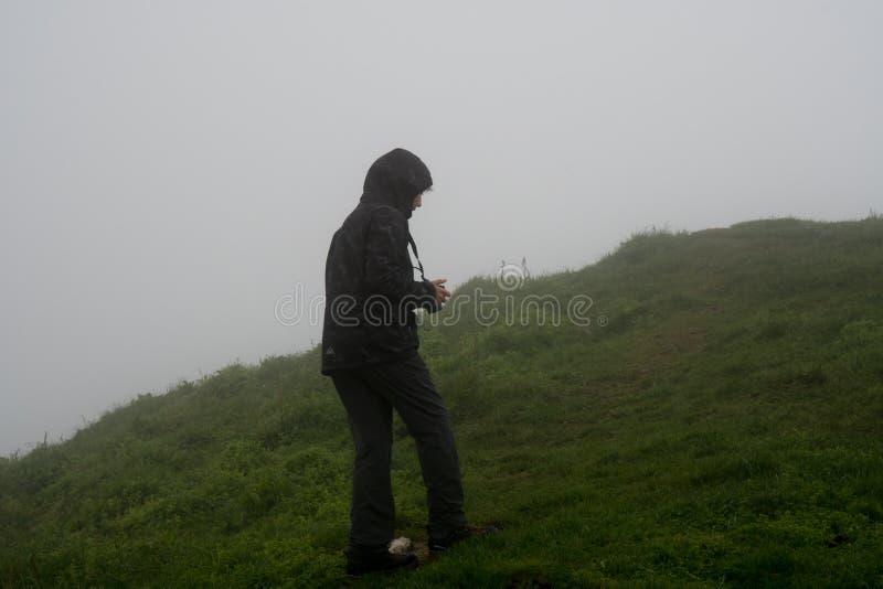 Fotograf des jungen Mädchens auf den Klippen von Mykines in Färöern lizenzfreies stockfoto