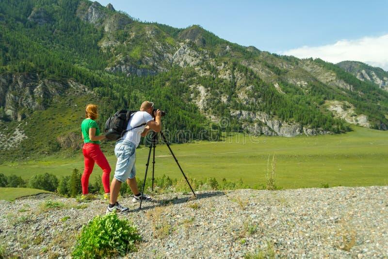 Fotograf des jungen Mannes und rotes behaartes Mädchen reist durch das A stockfotos