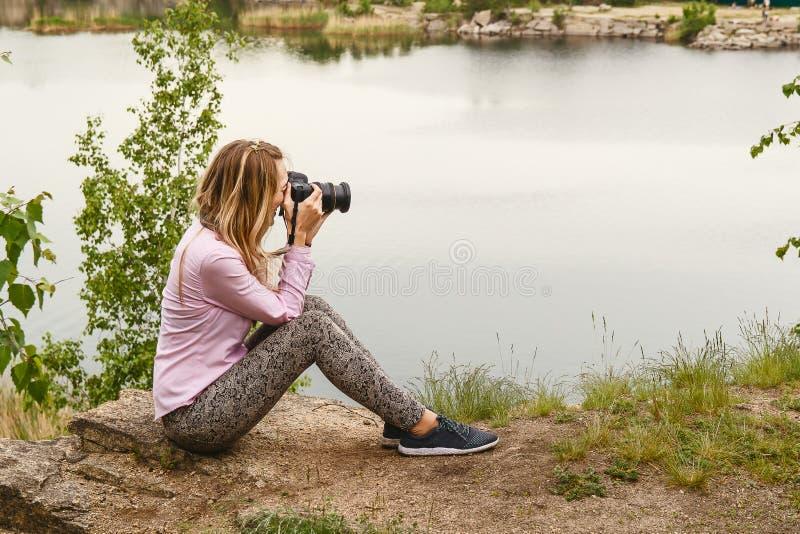 Fotograf f?r ung kvinna som tar bilder av naturen royaltyfria bilder