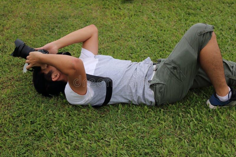 Fotograf för ung man som ligger på jordning för grönt gräs med hållande kameradslr i händerna fotografering för bildbyråer
