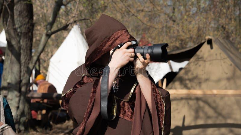 Fotograf i brun medeltida cloak med en huva som tar foto på den internationella ridfesten St George royaltyfri bild