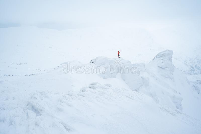 Fotograf i vintern som trekking på de snöig bergen fotografering för bildbyråer