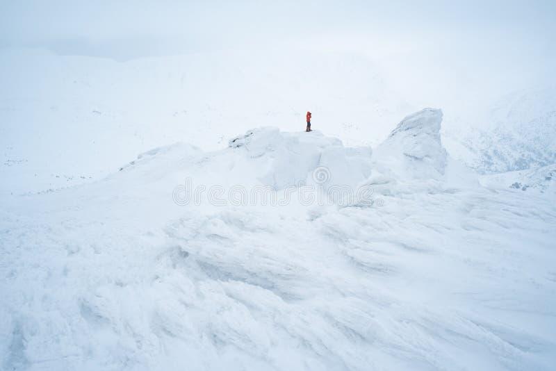 Fotograf i vintern som trekking på de snöig bergen arkivbild