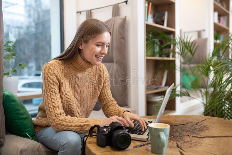 Fotograf lädt Bilder von der Kamera auf ihren Computer hoch stockfotos