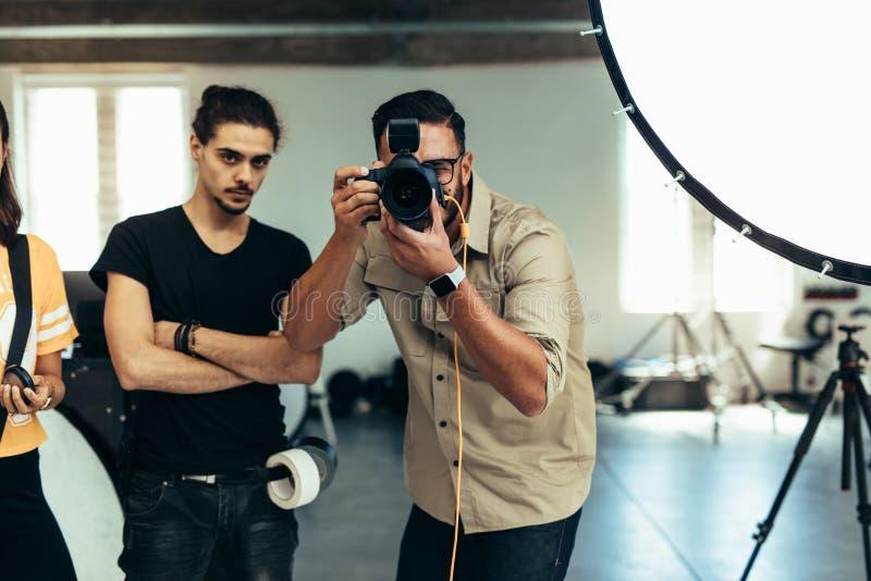 Fotograf med hans lag som gör en fotofors i en studio Fotograf som tar på ett fotografi med pråligt ljus för studio royaltyfria bilder