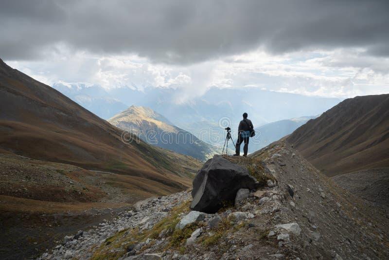 Fotograf med kameran och tripod i bergen royaltyfria bilder