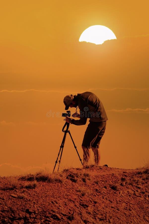Fotograf med kameran på tripoden som tar bilder på solnedgången royaltyfri bild