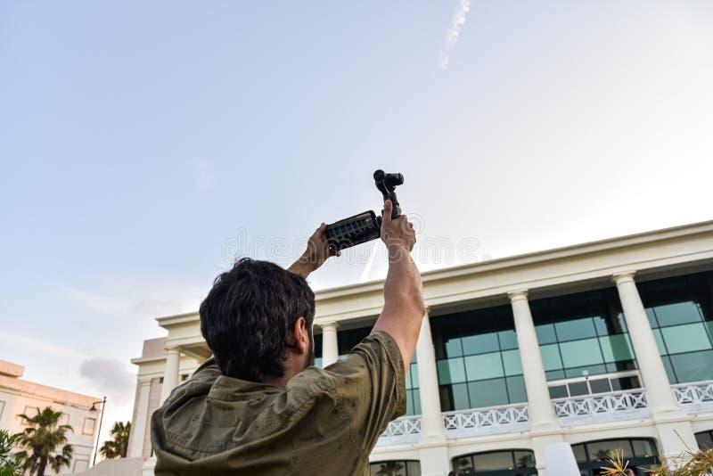 Fotograf mit einem Stabilisator für sein Handy beim Aufnehmen einer Videoszene lizenzfreies stockfoto