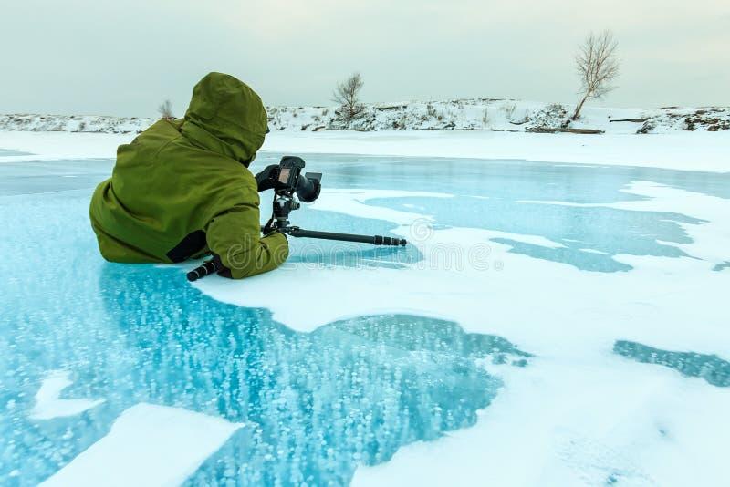 Fotograf nimmt die Bildblasen des Methangases eingefroren in Glatteis der Baikalsee, Russland lizenzfreies stockfoto