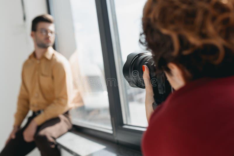 Fotograf och modell på fönstret arkivfoto