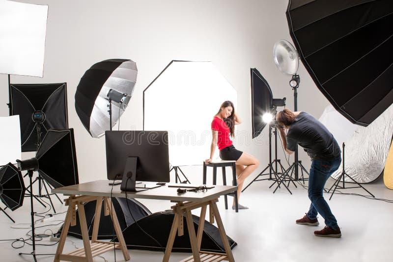 Fotograf och nätt modell som arbetar i modern belysningstudio arkivbilder