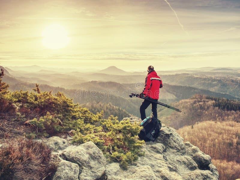 Fotograf på klippan med tripoden i hand tycka om den gammala fotografen f?r fem natur fotograferar att ta ?r royaltyfri bild