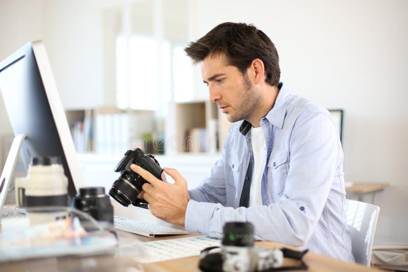 Fotograf på kontoret som kontrollerar skott royaltyfri fotografi