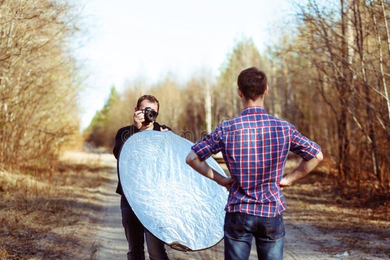 Fotograf Photographing Male Model i Forest Backstage av mode Photoshoot av den yrkesmässiga fotografen med DSLR royaltyfria foton