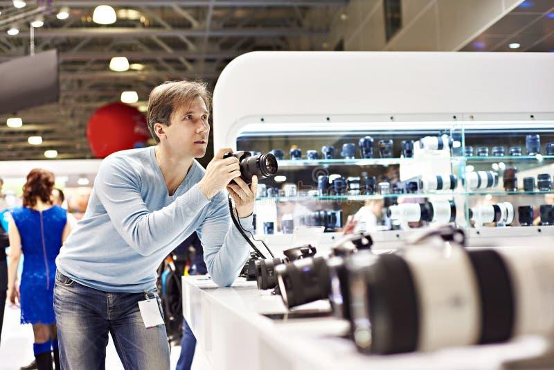 Fotograf prüft digitale SLR-Kamera in der Fotoausstellung lizenzfreie stockbilder