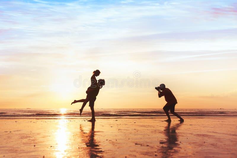 Fotograf som arbetar med par på stranden, yrkesmässigt bröllopfotografi arkivfoton