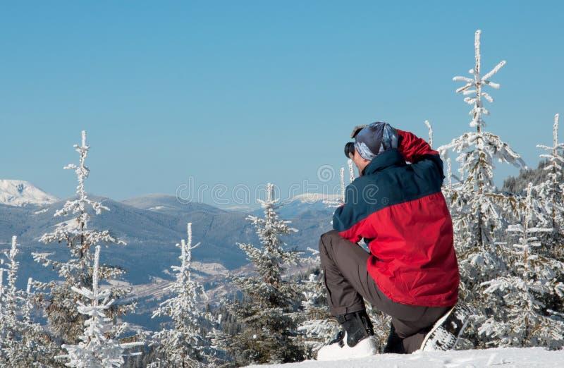 Fotograf som fotograferar vinterpanorama i höga berg arkivbild
