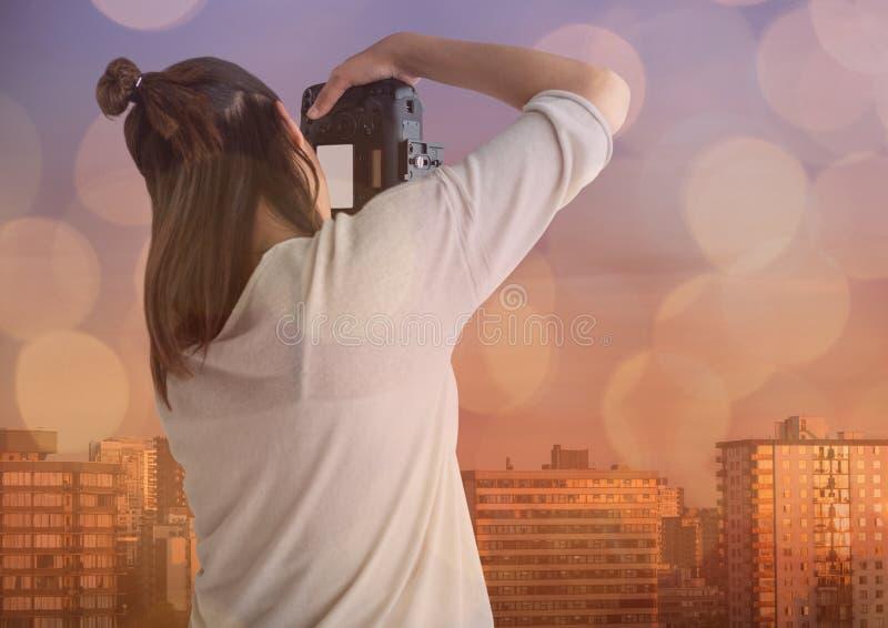 fotograf som framme tar ett foto (som är tillbaka) av staden Blå och orange bokehöverlappning royaltyfri bild