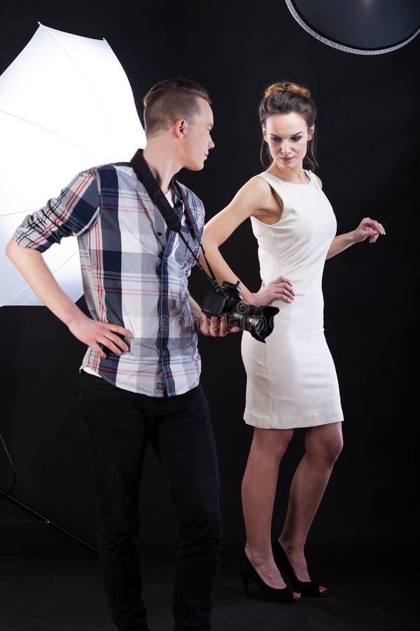 Fotograf som ger rådgivning till den kvinnliga modellen arkivfoto