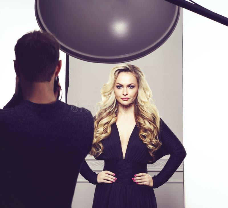 Fotograf som tar bilder av en härlig modell i studio arkivbilder