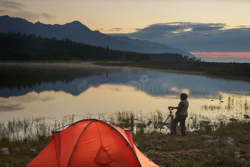 Fotograf som tar en bild av den härliga sjön och berget nära det orange tältet arkivfoto