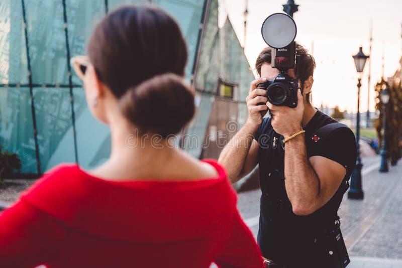 Fotograf som tar foto av den härliga modellen, i kulisserna av modephotoshoot och att ta headshoten och stående fotografering för bildbyråer