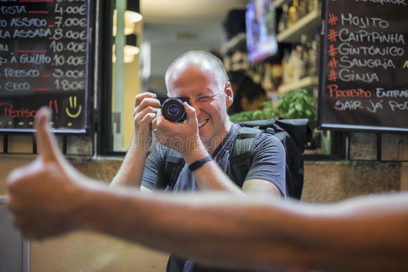 Fotograf som tar foto av livliga gator med restauranger arkivbilder