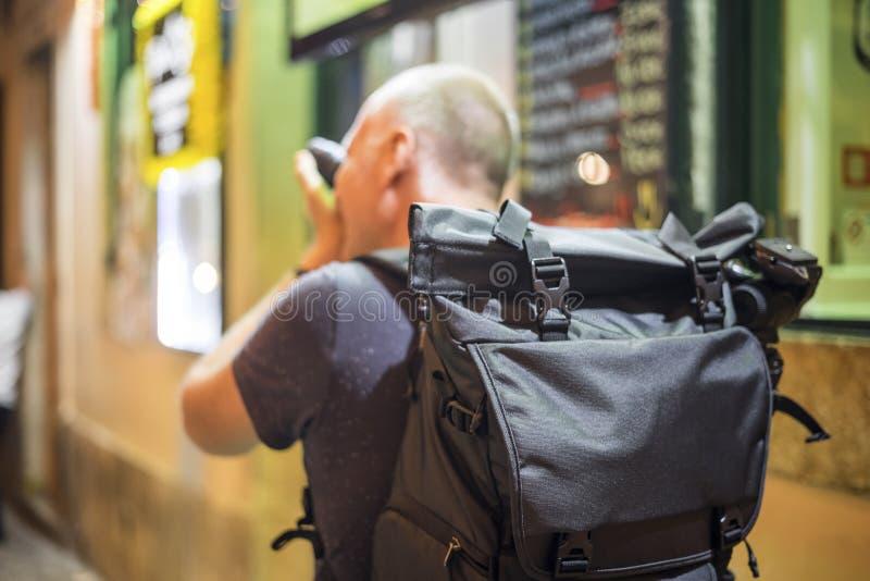 Fotograf som tar foto av livliga gator med restauranger arkivfoto